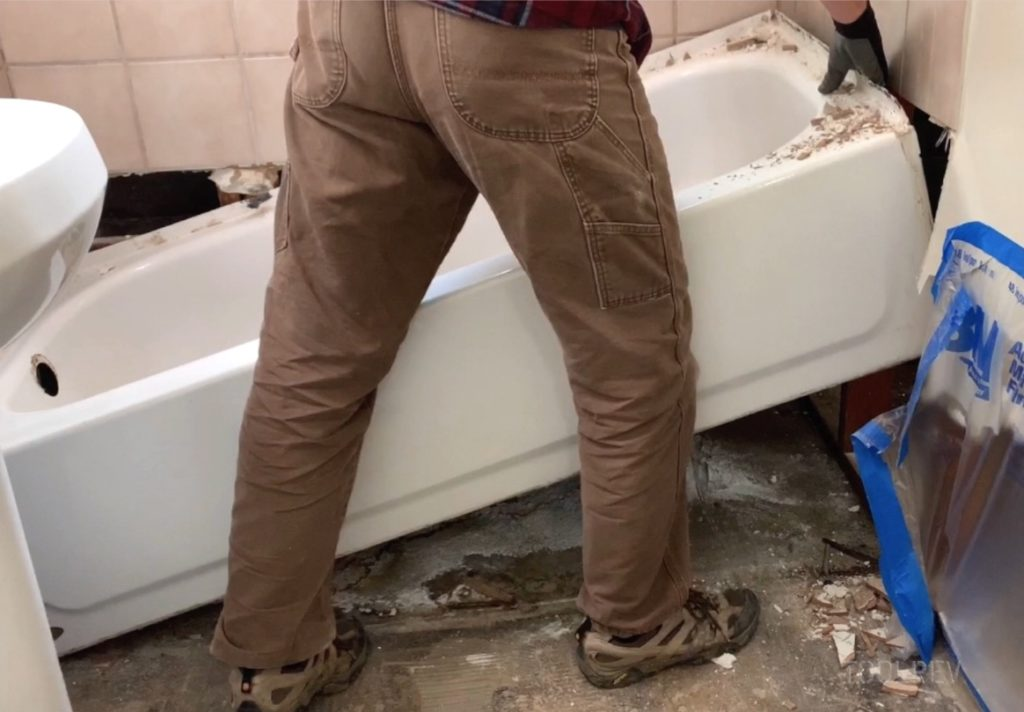 Worker lifting bathtub up from floor.
