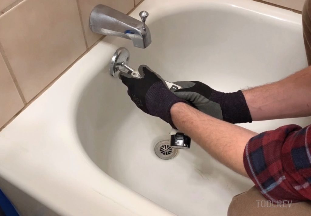Worker unscrewing bathtub overflow cover.