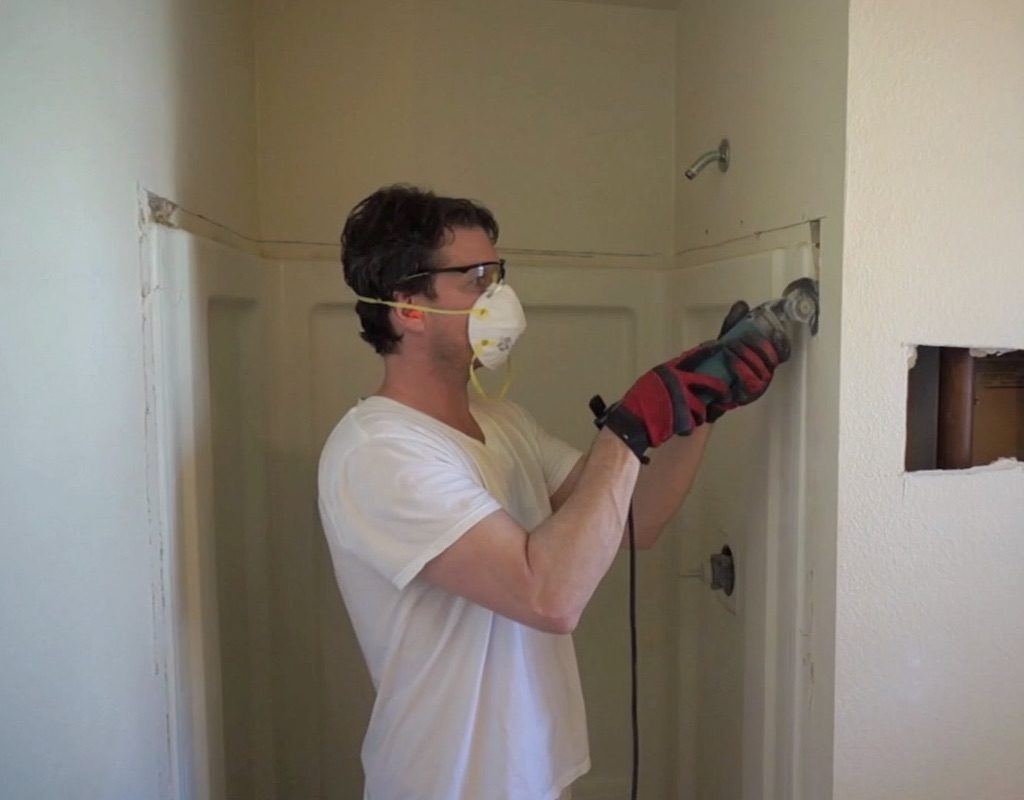 man in dust mask cutting out shower stall with power tool