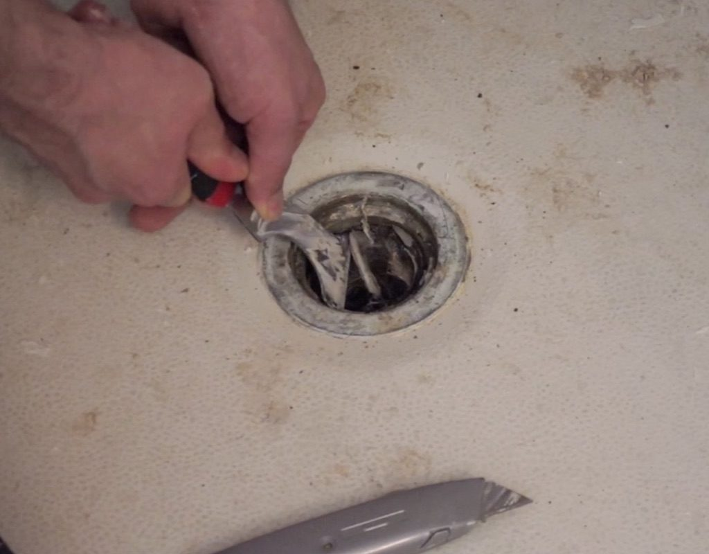 worker using a tool to remove caulking from shower drain