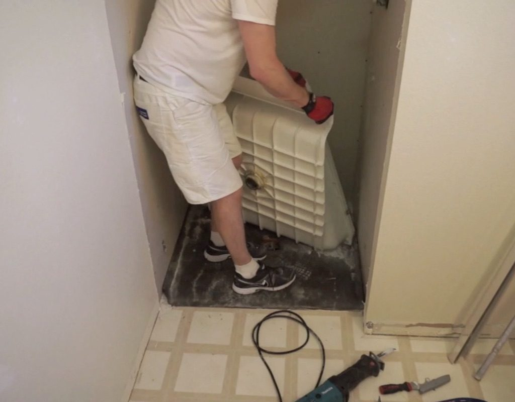 worker lifting shower pan out of shower stall