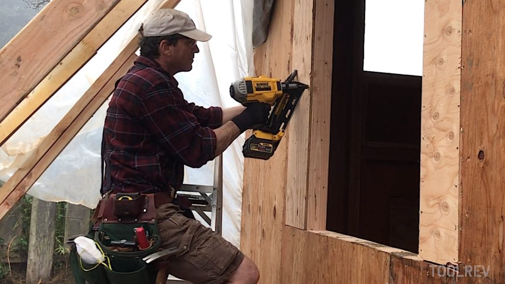 Man using framing nailer to attach wood siding to house