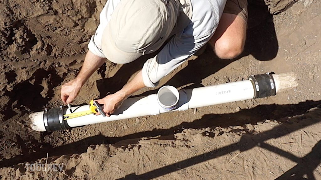 Worker measuring and marking PVC pipe with marker.