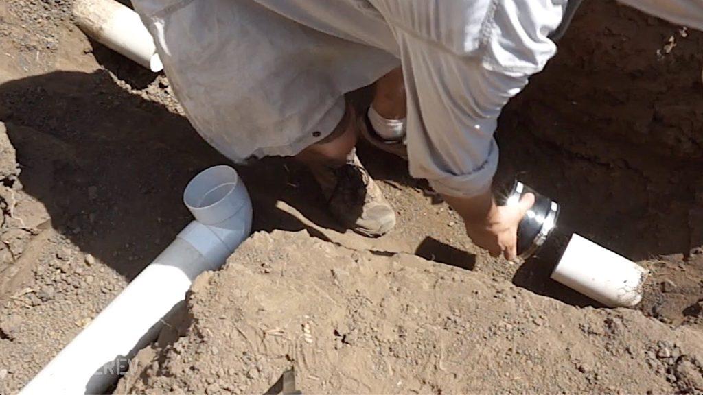 Man placing couplings over PVC drain pipe.