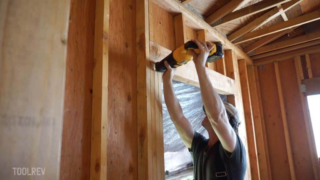 Man using DeWalt Flexvolt reciprocating saw to cut wood framing.